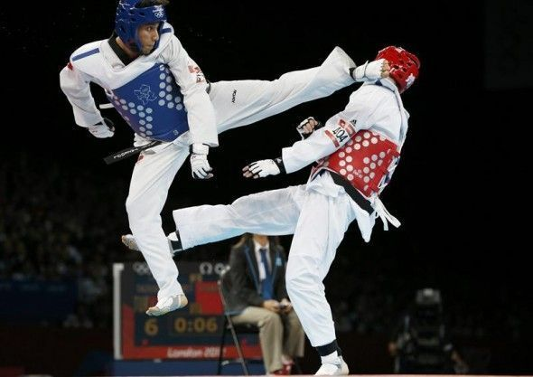 Turkey's Servet Tazegul kicks Britain's Martin Stamper during their men's -68kg semifinal taekwondo match at the London Olympic Games